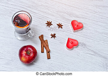 Mulled wine with spices on a lace napkin. Candles in the shape of a heart, cinnamon sticks and apple. Light wooden background