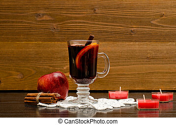 Mulled wine with spices on a lace napkin. Candles in the shape of a heart, cinnamon sticks and apple. Wood background