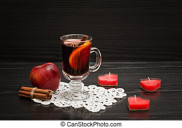 Mulled wine with spices on a lace napkin. Candles in the shape of a heart, cinnamon sticks and apple. Black wood background