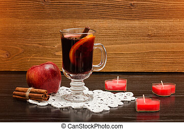 Mulled wine with spices on a lace napkin. Candles in the shape of a heart, cinnamon sticks and apple. Wooden background