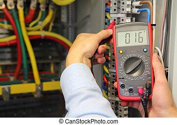multímetro, en, manos, de, electrician., verificar, voltaje, en, eléctrico, fusible, box.