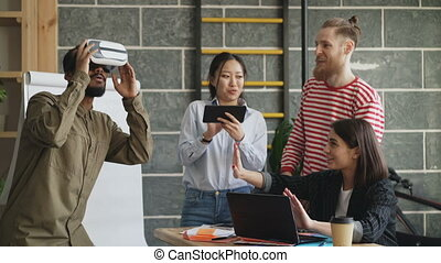 Mult ethnic team testing VR game simulator at modern office. African american man trying play virtual reality headset while asian girl using digital tablet