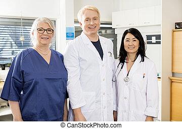 multiétnico, equipo médico, sonriente, juntos, en, hospital