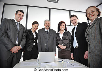Multi aged business people standing around the table at office