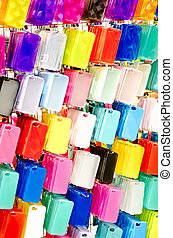 Multi Color plastic mobile phone cases on hangers .