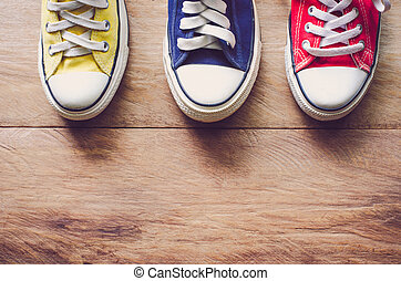 Multi Color sneakers on wood background