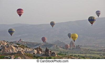 Multi-colored balloons fly over rocks. Cappadocia
