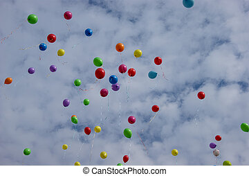 Multi-colored balloons in the sky with clouds