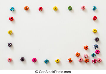 Multi colored beads on white background with copy sapce