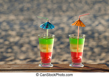 Multi-colored cocktails on a wooden table on the beach, the sand on the background