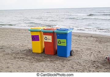 multi-colored containers for sorting garbage are on the beach ag