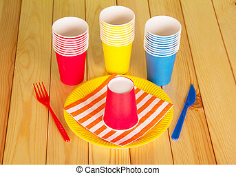 Multi-colored disposable cups on the background light wood...
