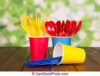 Multi-colored disposable plastic cups, forks, spoons on ...
