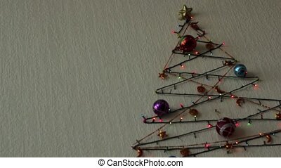Multi-colored flashing lights and Christmas tree balls on the wall in the form of a Christmas tree