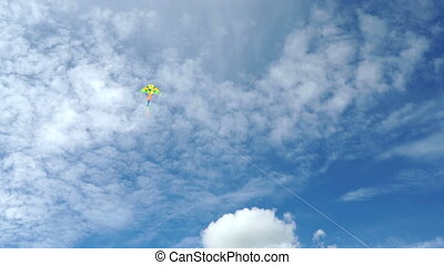 Multi-colored flying kite in a beautiful blue sky