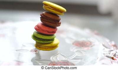 multi-colored macaroon cookies falls on the plate