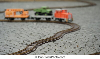 Multi colored model of freight train travels along the winding rails of the railway. Close up side ground view