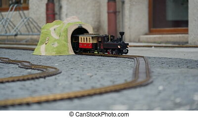 Multi-colored model of locomotive moves through the yellow toy arch or tunnel