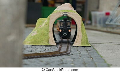 Multi-colored model of locomotive moves through the yellow toy arch or tunnel, close up