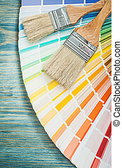 Multi colored pantone fan paint brushes on wooden board construc