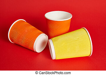 Multi-colored paper cups for a hot drink lying on a red background with copy space. Shot with soft shadow. Recyclable cardboard mugs.