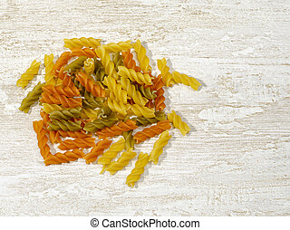 multi-colored pasta scattered on the kitchen table.