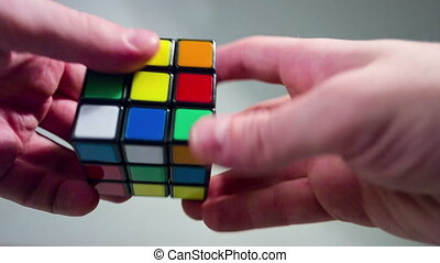 Multi colored rubic cube in hands