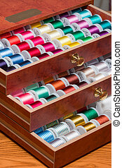 Multi Colored Spools of Sewing Thread in a Decorative Wooden Box