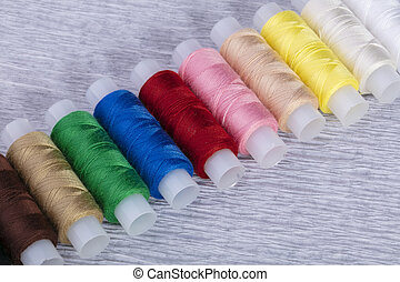 Multi-colored spools of thread on a gray background.