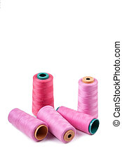 Multi-colored spools of thread on a white background