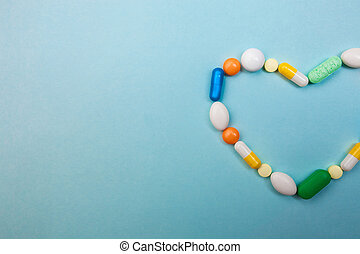 Multi-colored tablets and heart-shaped capsules, white bottle for tablets, pharmaceutical medicine pills on blue background, an analgesic against diseases