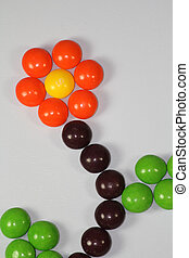 Multi-coloured candies arranged in form of plant with flower in a pot on white background