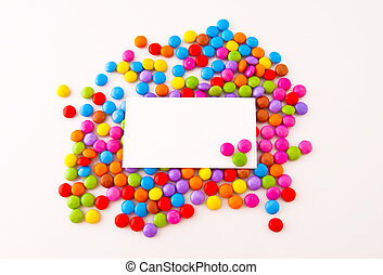 Multi-coloured chocolate candy on a white background and a card for an inscription
