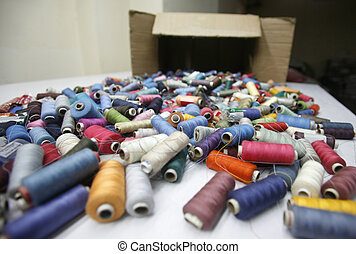 Multi coloured reels of cotton thread layed out on table
