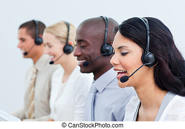 Multi-cultural business people working in a call center in...