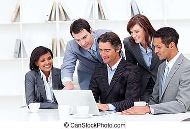 Multi-cultural business team looking at a laptop in the ...