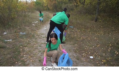 Group of responsible multiracial volunteers in green shirts picking up plastic rubbish scattered among forest. Positive diverse people taking care of natural environment and cleaning forest of garbage