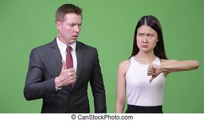 Multi-ethnic business couple having different decisions -...