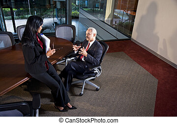 Multi-ethnic business executives having discussion in boardroom