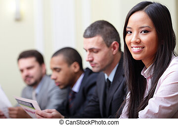 Multi ethnic business executives working with documents. ...