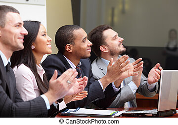 Multi ethnic business group greets somebody with clapping and smiling. Focus on african-american man