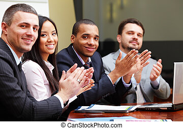 Multi ethnic business group greets you with clapping and...