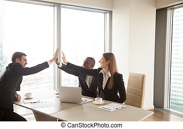 Multi-ethnic business partners giving high five on meeting, cele