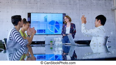 Side view of multi-ethnic business people applauding Caucaisan businesswoman in modern office. She is using digital tablet 4k