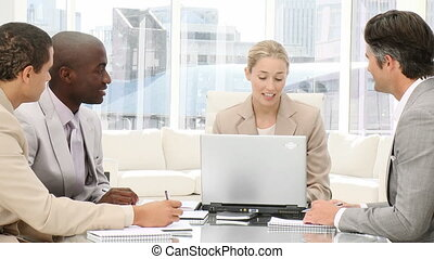 Multi-ethnic business people working at a computer in a meeting
