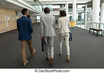 Multi-ethnic business people interacting with each other while walking on office floor