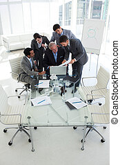 Multi-ethnic business people looking at a document