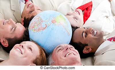 Multi-ethnic business people lying around a globe -...