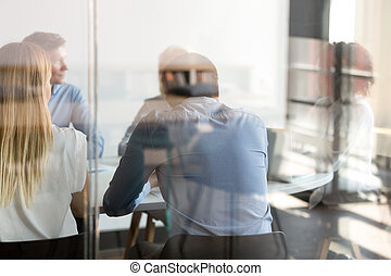 Multi ethnic business people negotiating at table view through glass