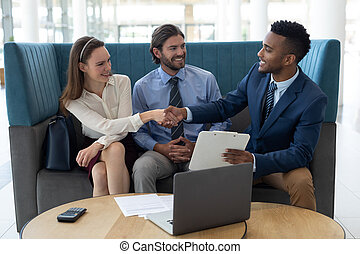 Multi-ethnic business people shaking hands with each other in the lobby